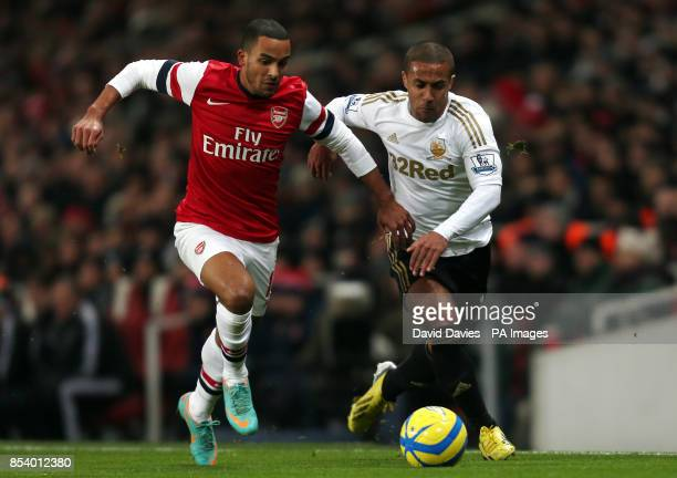Arsenal's Theo Walcott tussles for the ball with Swansea's Wayne Routledge during the FA Cup Third Round Replay at the Emirates Stadium London