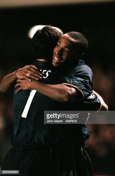 Arsenal's Thierry Henry celebrates with teammate Robert Pires after the second goal of the game
