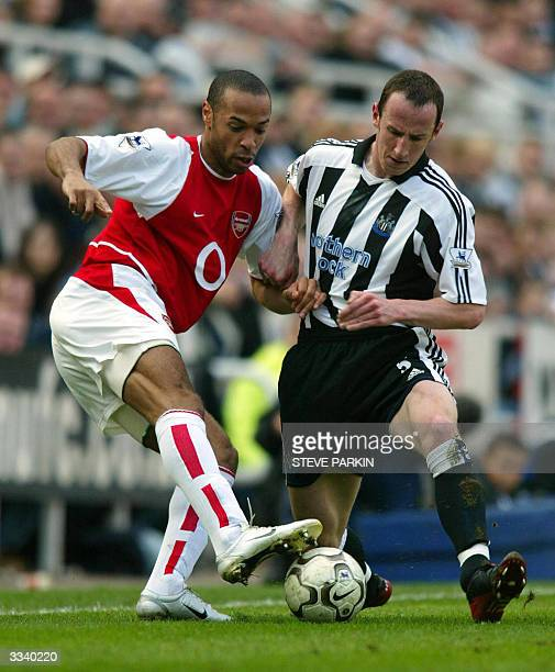 Arsenal's Thierry Henry is tackled by Newcastle's Andy O'Brien during their premiership clash at St James Park Newcastle 11 April 2004 AFP...