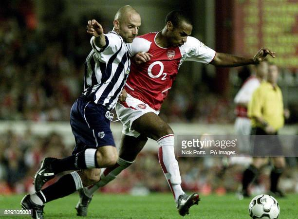 Arsenal's Thierry Henry tussles with West Bromwich Albion defender Larus Sigurdsson for the ball during the FA Barclaycard Premiership game at...