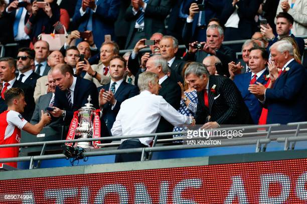 Arsenal's US owner Stan Kroenke shakes hands with Arsenal's French manager Arsene Wenger as Arsenal players celebrate their victory over Chelsea in...
