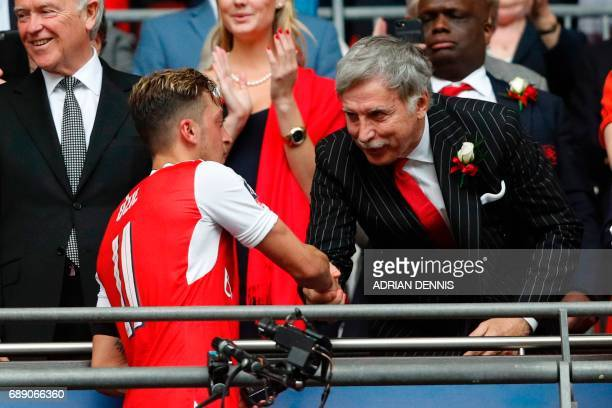 Arsenal's US owner Stan Kroenke shakes hands with Arsenal's German midfielder Mesut Ozil as Arsenal players celebrate their victory over Chelsea in...