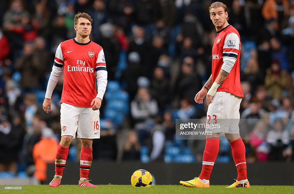 Arsenal's Welsh midfielder Aaron Ramsey (L) and Arsenal's Danish striker Nicklas Bendtner (R) react after the sixth Manchester City goal during the English Premier League football match between Manchester City and Arsenal at the Etihad Stadium in Manchester, northwest England, on December 14, 2013. Manchester City won 6-3. USE. No use with unauthorized audio, video, data, fixture lists, club/league logos or live services. Online in-match use limited to 45 images, no video emulation. No use in betting, games or single club/league/player publications.