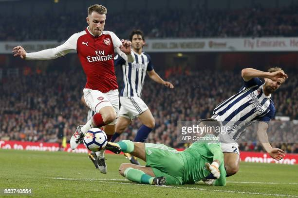 Arsenal's Welsh midfielder Aaron Ramsey attempts to run the ball past West Bromwich Albion's English goalkeeper Ben Foster but fails to score during...