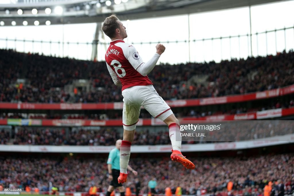 Arsenal's Welsh midfielder Aaron Ramsey celebrates after scoring their second goal during the English Premier League football match between Arsenal and Swansea City at the Emirates Stadium in London on October 28, 2017. / AFP PHOTO / Daniel LEAL-OLIVAS / RESTRICTED TO EDITORIAL USE. No use with unauthorized audio, video, data, fixture lists, club/league logos or 'live' services. Online in-match use limited to 75 images, no video emulation. No use in betting, games or single club/league/player publications. /