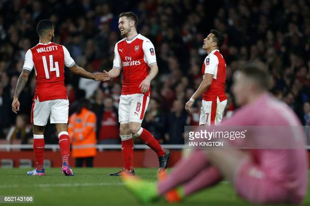 Arsenal's Welsh midfielder Aaron Ramsey celebrates with Arsenal's English midfielder Theo Walcott after scoring their fifth goal during the English...