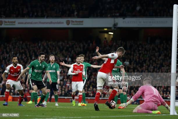 Arsenal's Welsh midfielder Aaron Ramsey goes around Lincoln City's English goalkeeper Paul Farman on his way to scoring their fifth goal during the...