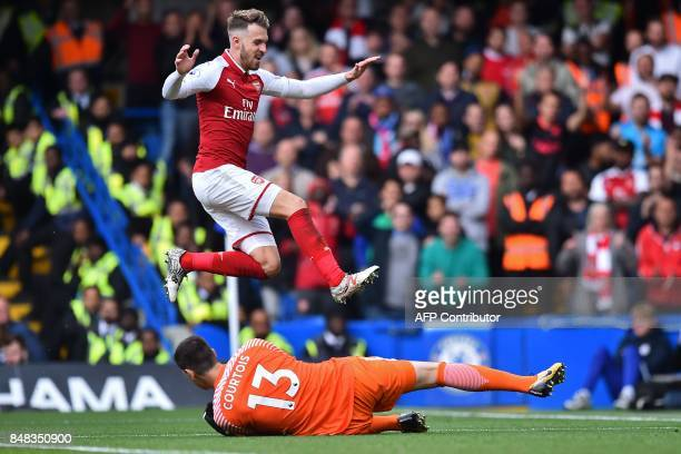 Arsenal's Welsh midfielder Aaron Ramsey jumps over the save from Chelsea's Belgian goalkeeper Thibaut Courtois during the English Premier League...