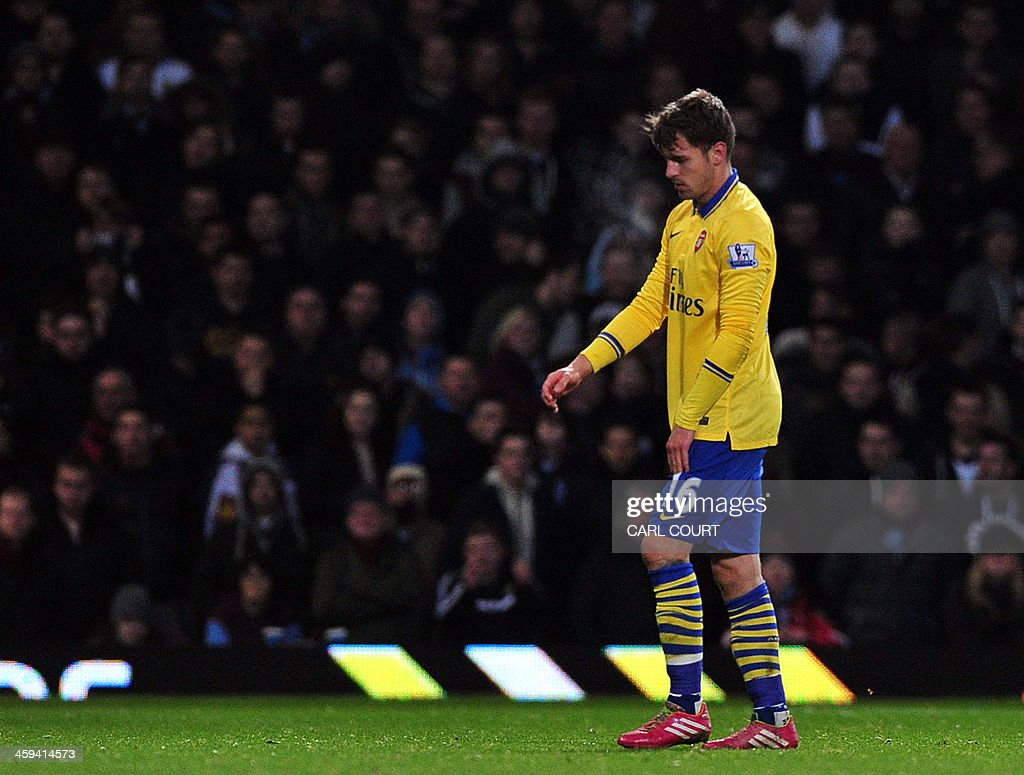Arsenal's Welsh midfielder Aaron Ramsey leaves the pitch, injured during the English Premier League football match between West Ham United and Arsenal at the Boleyn Ground, Upton Park, in east London on December 26, 2013. Arsenal won the game 3-1. USE. No use with unauthorized audio, video, data, fixture lists, club/league logos or live services. Online in-match use limited to 45 images, no video emulation. No use in betting, games or single club/league/player publications.