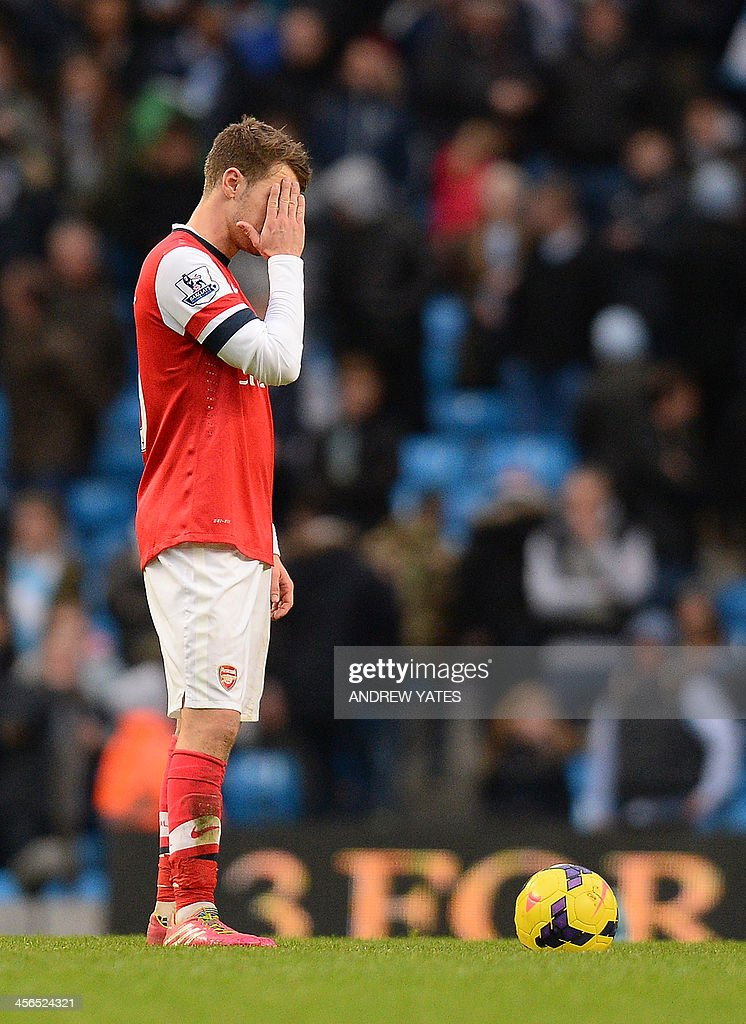 Arsenal's Welsh midfielder Aaron Ramsey reacts after the sixth Manchester City goal during the English Premier League football match between Manchester City and Arsenal at the Etihad Stadium in Manchester, northwest England, on December 14, 2013. Manchester City won 6-3. USE. No use with unauthorized audio, video, data, fixture lists, club/league logos or live services. Online in-match use limited to 45 images, no video emulation. No use in betting, games or single club/league/player publications.