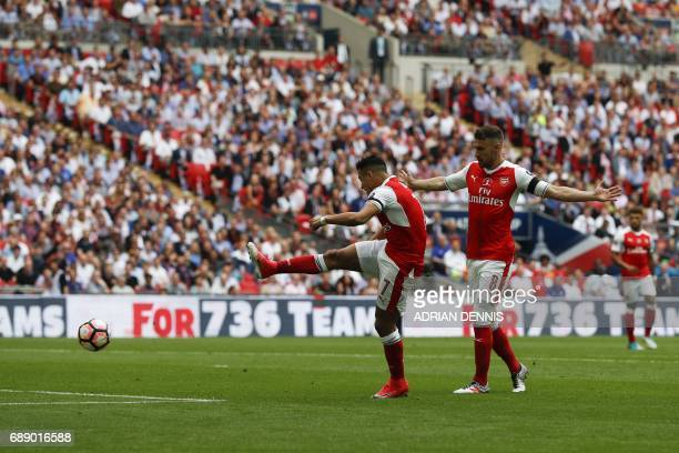 Arsenal's Welsh midfielder Aaron Ramsey stands back and lets Arsenal's Chilean striker Alexis Sanchez shoot and score the opening goal of the English...