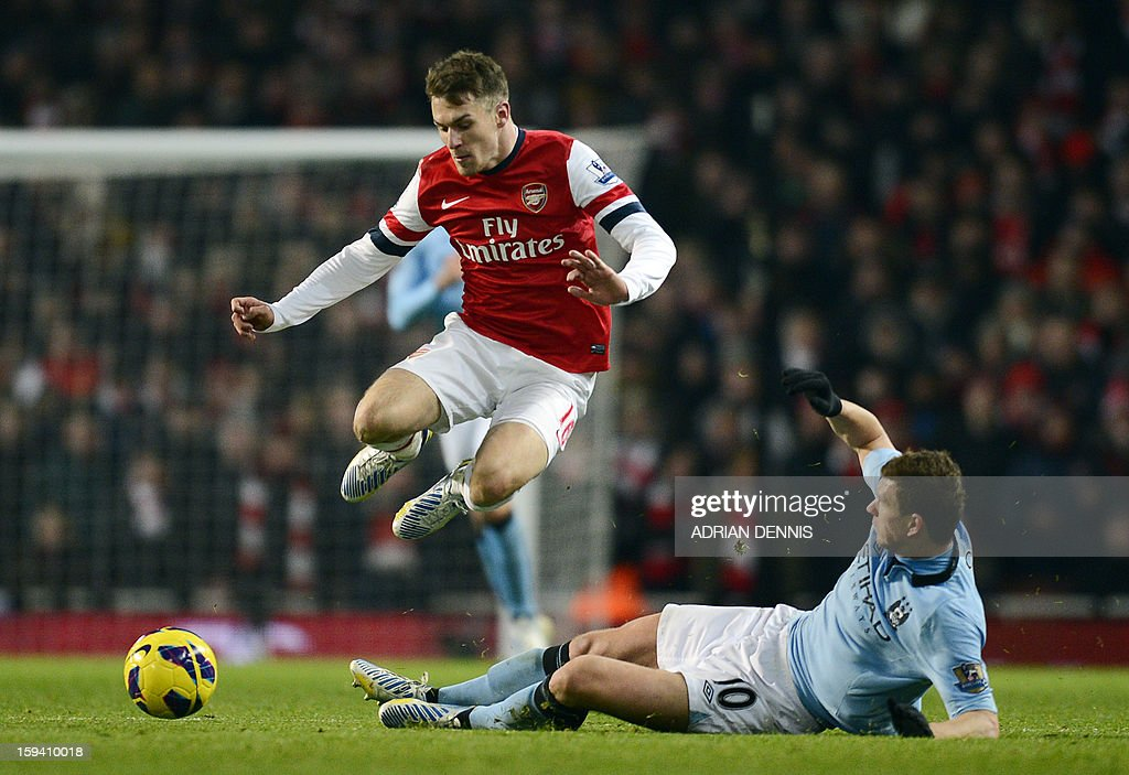 Arsenal's Welsh midfielder Aaron Ramsey (L) vies with Manchester City's Bosnian striker Edin Dzeko (R) during their English Premier League football match at the Emirates Stadium in London on January 13, 2013. USE. No use with unauthorized audio, video, data, fixture lists, club/league logos or 'live' services. Online in-match use limited to 45 images, no video emulation. No use in betting, games or single club/league/player publications.
