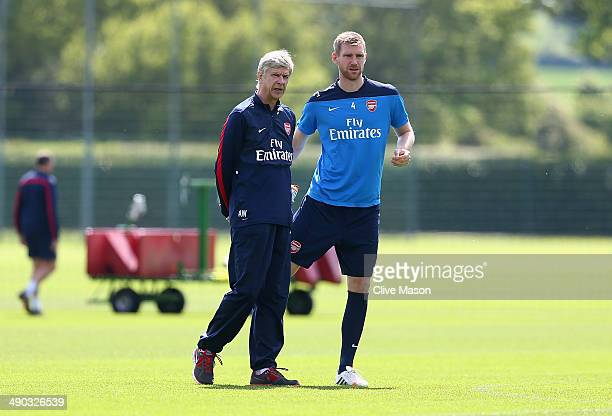 Arsene Wenger and Per Mertesacker of Arsenal look on during a training session ahead of the FA Cup Final match between Arsenal and Hull City at...