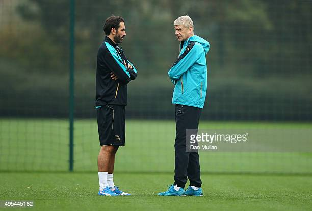 Arsene Wenger manager of Arsenal and exArsenal player Robert Pires in discussion during an Arsenal training session on the eve of the UEFA Champions...