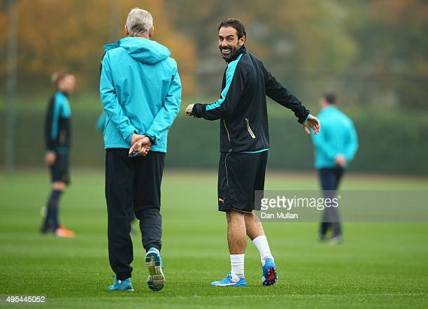 Arsene Wenger manager of Arsenal and exArsenal player Robert Pires look on during an Arsenal training session on the eve of the UEFA Champions League...