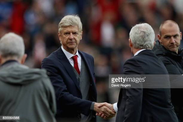 Arsene Wenger Manager of Arsenal and Mark Hughes Manager of Stoke City shake hands after the Premier League match between Stoke City and Arsenal at...