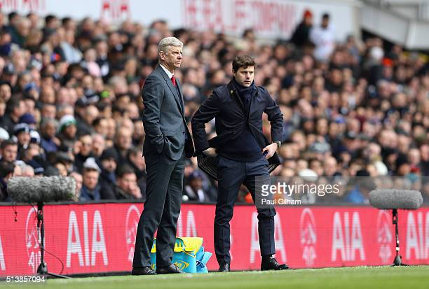 Arsene Wenger Manager of Arsenal and Mauricio Pochettino Manager of Tottenham Hotspur look on during the Barclays Premier League match between...