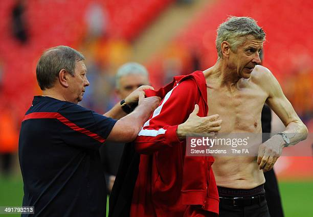 Arsene Wenger manager of Arsenal changes his shirt after being covered with beer following victory in the FA Cup with Budweiser Final match between...