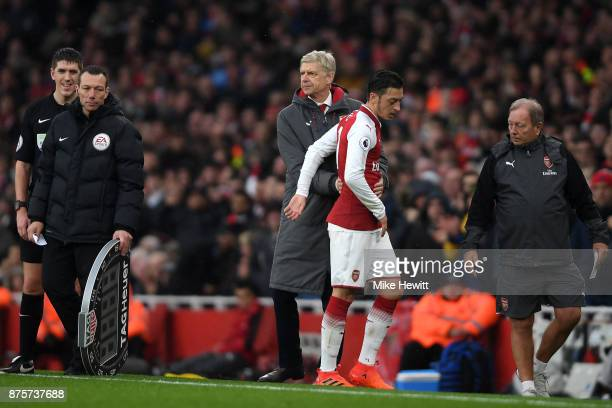 Arsene Wenger Manager of Arsenal embraces Mesut Ozil after the player was substituted during the Premier League match between Arsenal and Tottenham...
