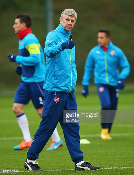 Arsene Wenger manager of Arsenal gives a thumbs up during an Arsenal training session ahead of the UEFA Champions League Group D match against...