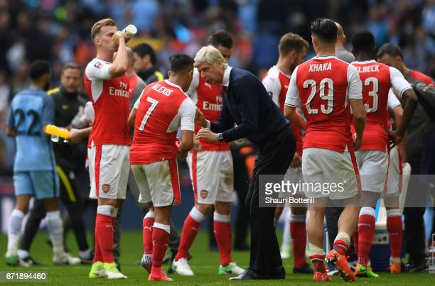 Arsene Wenger manager of Arsenal instructs Alexis Sanchez during the Emirates FA Cup SemiFinal match between Arsenal and Manchester City at Wembley...