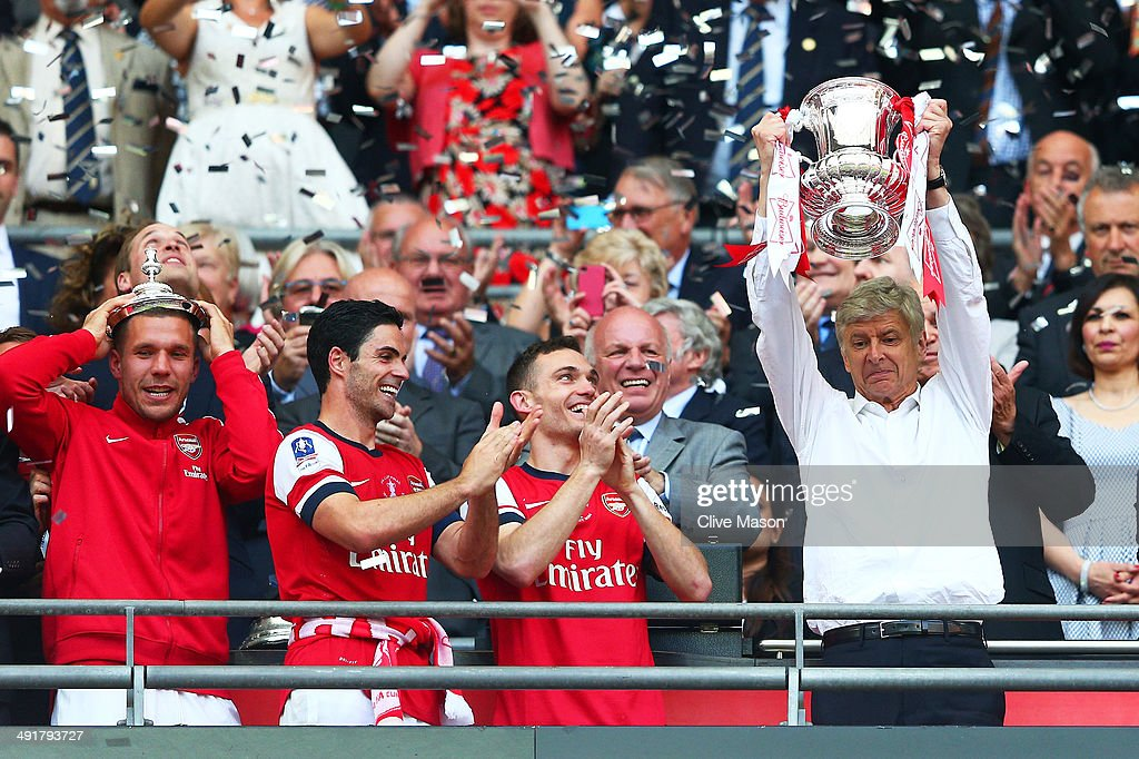 Arsene Wenger manager of Arsenal lifts the trophy in celebration alongside Lukas Podolski Mikel Arteta and Thomas Vermaelen after the FA Cup with...