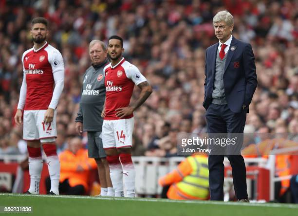 Arsene Wenger manager of Arsenal looks on as Olivier Giroud and Theo Walcott of Arsenal prepare to come on during the Premier League match between...