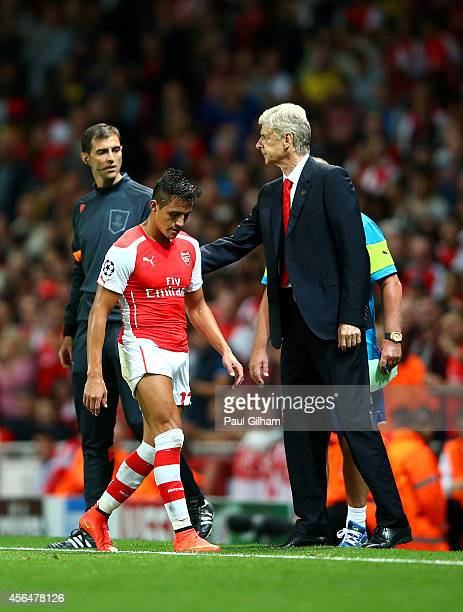 Arsene Wenger manager of Arsenal pats Alexis Sanchez of Arsenal on the back as he is substituted for David Ospina after Wojciech Szczesny received a...