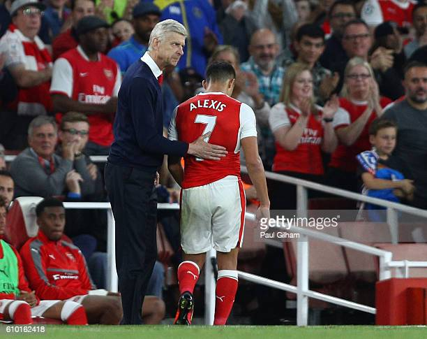 Arsene Wenger Manager of Arsenal pats Alexis Sanchez of Arsenal on the back after he is subbed during the Premier League match between Arsenal and...