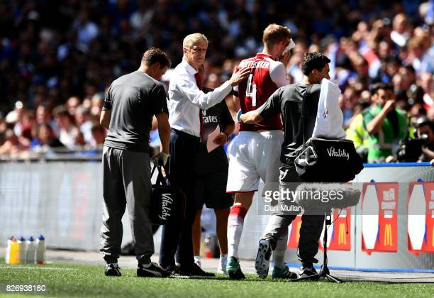 Arsene Wenger Manager of Arsenal pats Per Mertesacker of Arsenal on the back as he receives treatment from the medical team during the The FA...