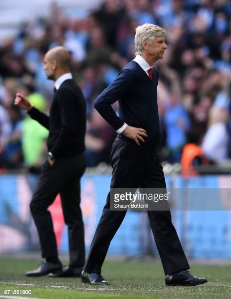 Arsene Wenger manager of Arsenal reacts while Josep Guardiola manager of Manchester City celebrates as Sergio Aguero of Manchester City scores the...