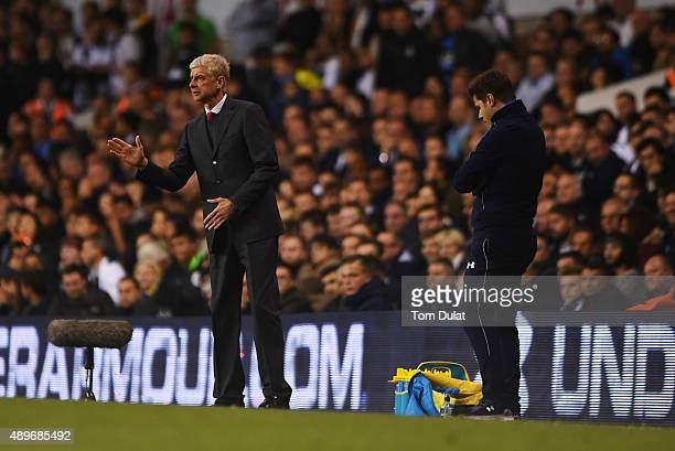 Arsene Wenger manager of Arsenal signals as Mauricio Pochettino manager of Tottenham Hotspur looks on during the Capital One Cup third round match...