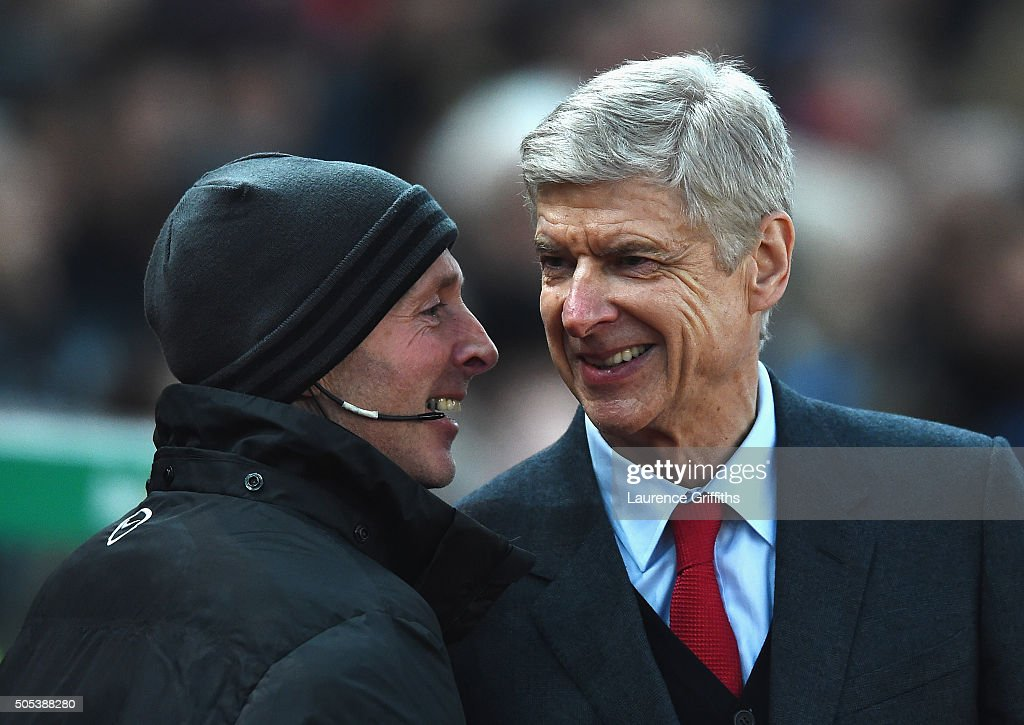 Arsene Wenger, manager of Arsenal smiles with fourth official Mike Dean prior to the Barclays Premier League match between Stoke City and Arsenal at Britannia Stadium on January 17, 2016 in Stoke on Trent, England.