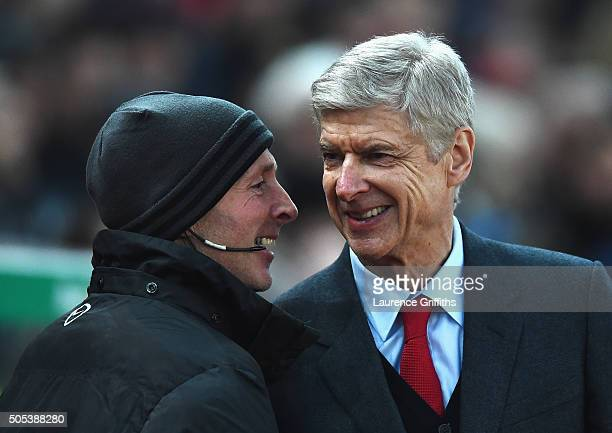 Arsene Wenger manager of Arsenal smiles with fourth official Mike Dean prior to the Barclays Premier League match between Stoke City and Arsenal at...