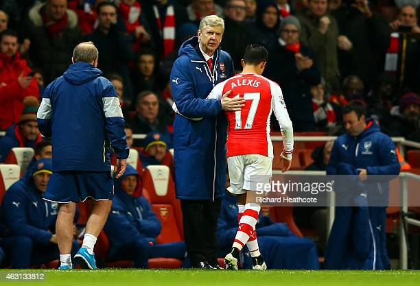 Arsene Wenger manager of Arsenal speaks with Alexis Sanchez of Arsenal as he is substituted during the Barclays Premier League match between Arsenal...