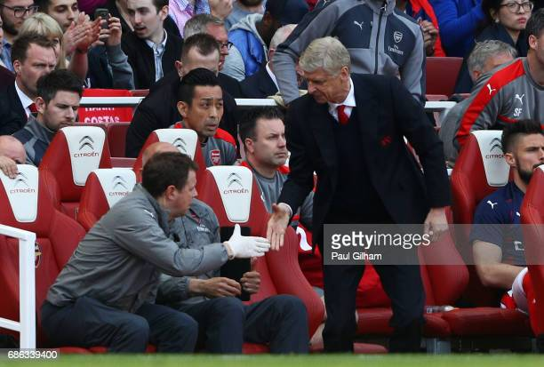 Arsene Wenger Manager of Arsenal speaks with his backroom staff during the Premier League match between Arsenal and Everton at Emirates Stadium on...