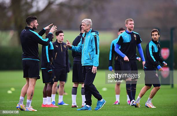 Arsene Wenger manager of Arsenal talks to Olivier Giroud during an Arsenal training session ahead of the UEFA Champions League match against...