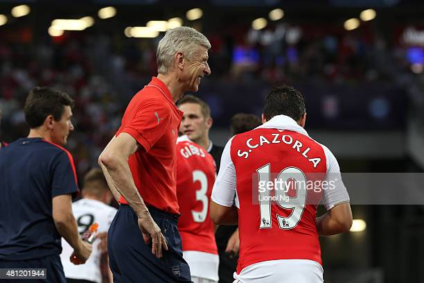 Arsene Wenger of Arsenal smiles at Santi Cazorla of Arsenal during the Barclays Asia Trophy match between Arsenal and Everton at the National Stadium...