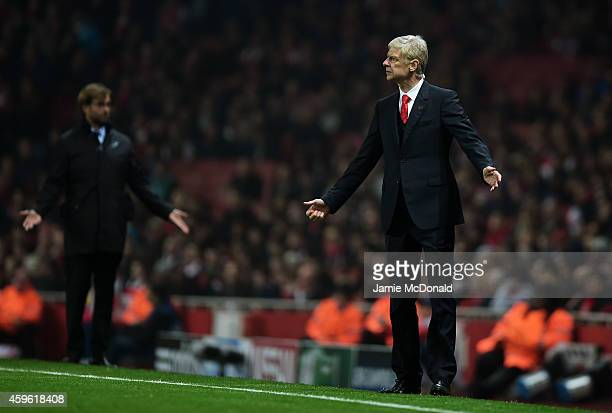 Arsene Wenger the Arsenal manager and Jurgen Klopp the Borussia Dortmund manager gesture during the UEFA Champions League Group D match between...