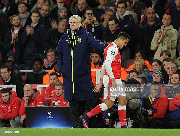 Arsene Wenger the Arsenal Manager pats Alexis Sanchez of Arsenal on the back after substituting him during the UEFA Champions League match between...
