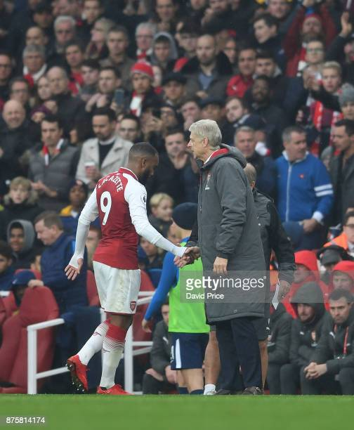 Arsene Wenger the Arsenal Manager shakes hands with Alexandre Lacazette as he comes off as a sub during the Premier League match between Arsenal and...