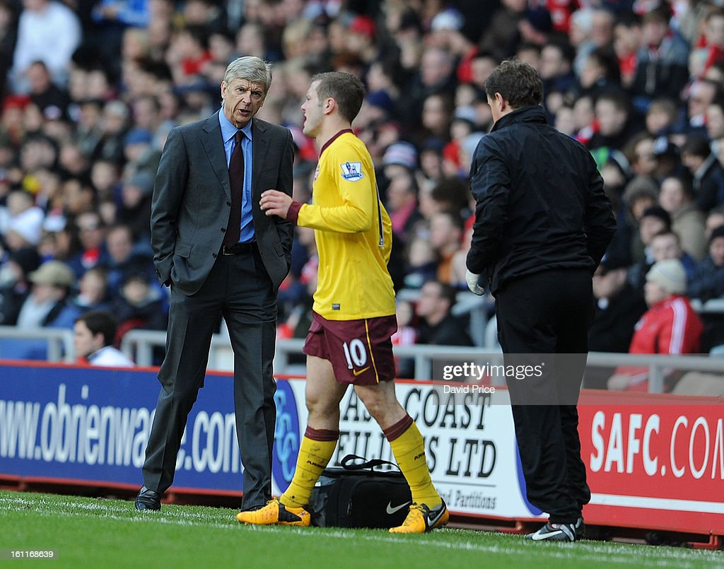 Arsene Wenger the Manager of Arsenal chats to Jack Wilshere as he is checked out by the Physio Colin Lewin during the Barclays Premier League match between Sunderland and Arsenal at Stadium of Light on February 09, 2013 in Sunderland, England.