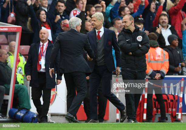Arsene Wenger the Manager of Arsenal shakes hands with Mark Hughes the Manager of Stoke during the Premier League match between Stoke City and...