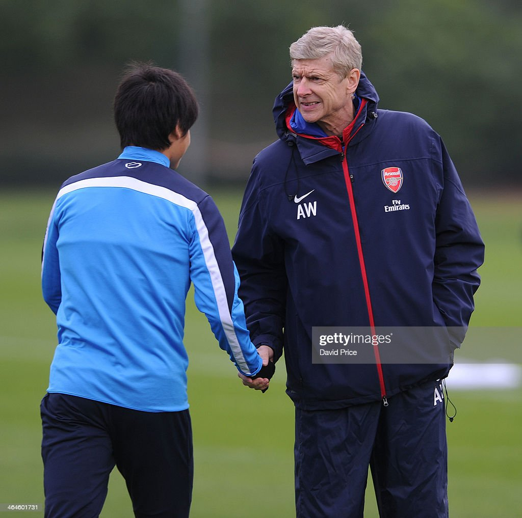Arsene Wenger the manager of Arsenal shakes hands with Ryo Miyaichi before Arsenal Training Session at London Colney on January 23, 2014 in St Albans, England.
