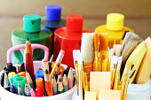 Artist painting supplies: paint brushes, sponge brushes, colored pencils, pens, markers and paint containers. Arts and crafts supplies.