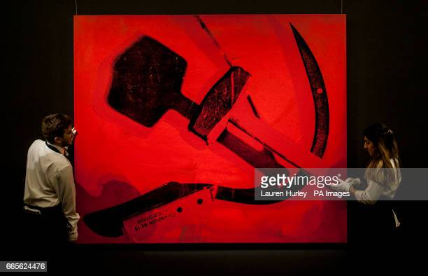Art handlers at Sotheby's in London hold Andy Warhol's 'Hammer and Sickle' 1976 estimated at between six and eight million dollars during a preview...