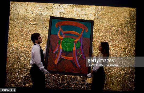 Art handlers at Sotheby's in London hold David Hockney's 'Gauguin's Chair' estimated at between 25 and 35 million dollars infront of Rudolf Stingel's...