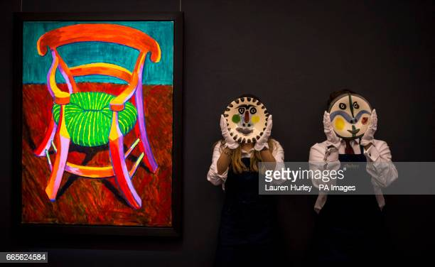Art handlers at Sotheby's in London hold two 'terre de faience' plates by Pablo Picasso two of 500 made next to David Hockney's 'Gauguin's Chair'...