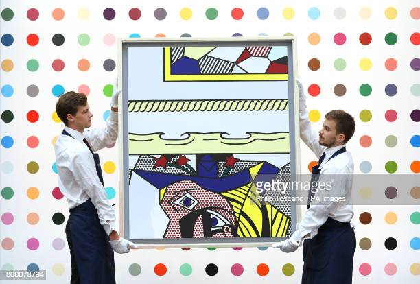 Art handlers carrying 'Two Paintings with Dado' by Roy Lichtenstein walk past Heptene by Damien Hirst two of the artworks on sale at the Sotheby's...
