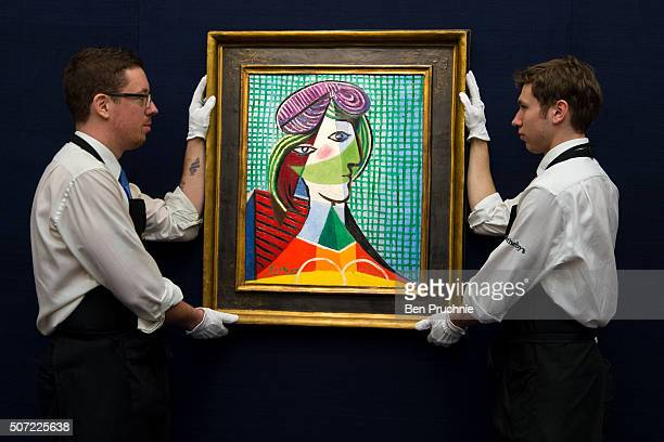 Art handlers hang Tete De Femme by Pablo Picasso which is up for auction for an estimated GBP 16000 to 20000 at Sotheby's on January 28 2016 in...